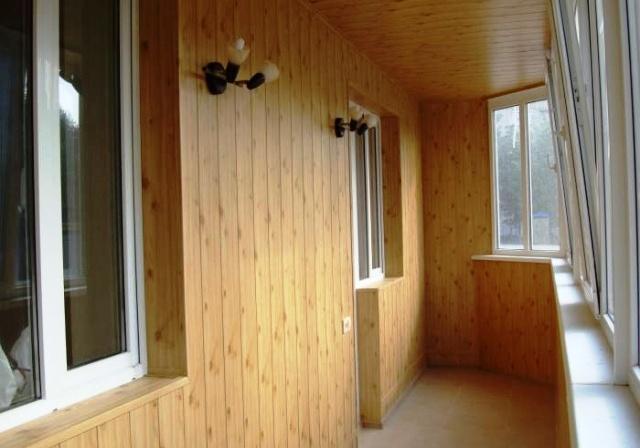 большой светлый балкон, отделанный вагонкой, с белыми пластиковыми окнами, двумя светильниками