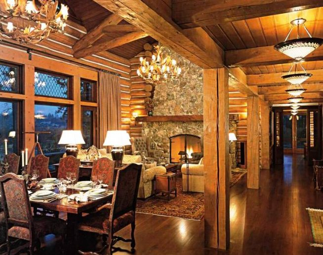 гостиная комната в бревенчатом доме с большим обеденным столом, крупными люстрами и камином с зажженным огнем