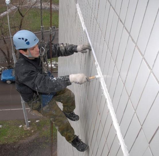 Рабочий выполняет герметизацию швов на наружной стене дома