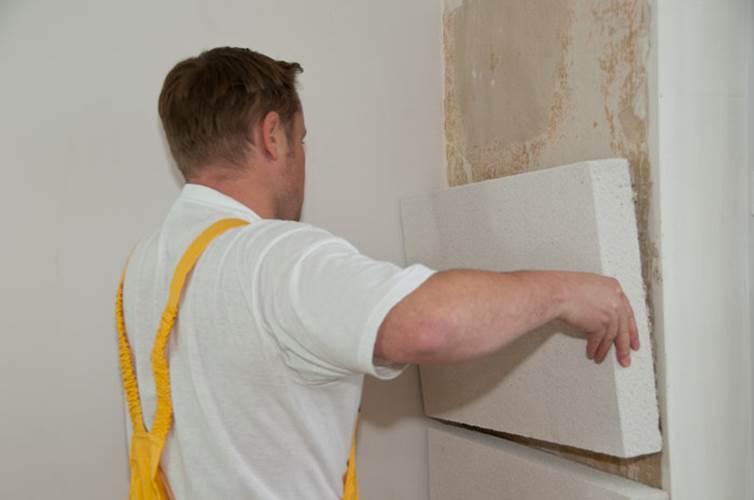 Мужчина утепляет стены пенопластом