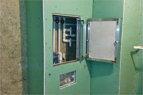 конструкция из гипсокартора зеленого цвета маскирует трубы в ванной