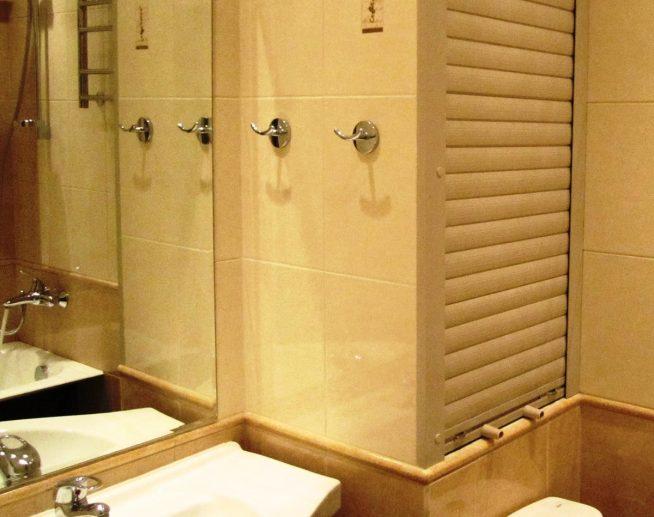 рольставни бежевого цвета маскируют трубы в ванной