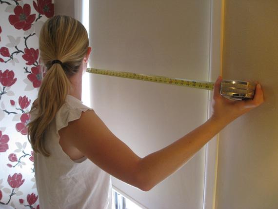 Девушка замеряет ширину обоев