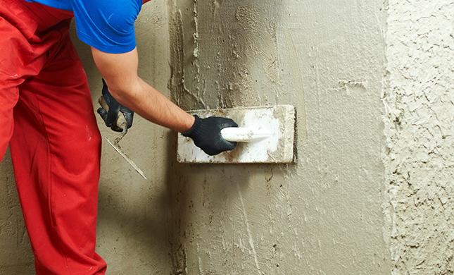 Рабочий штукатурит стену