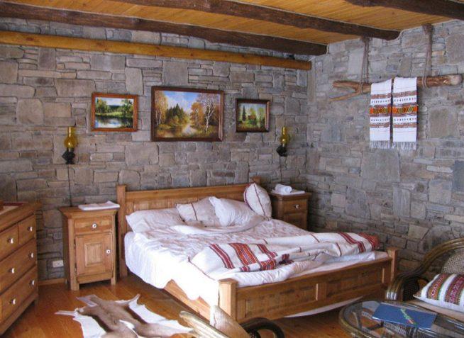 Натуральный камень и потолочные балки в интерьере спальни-шале