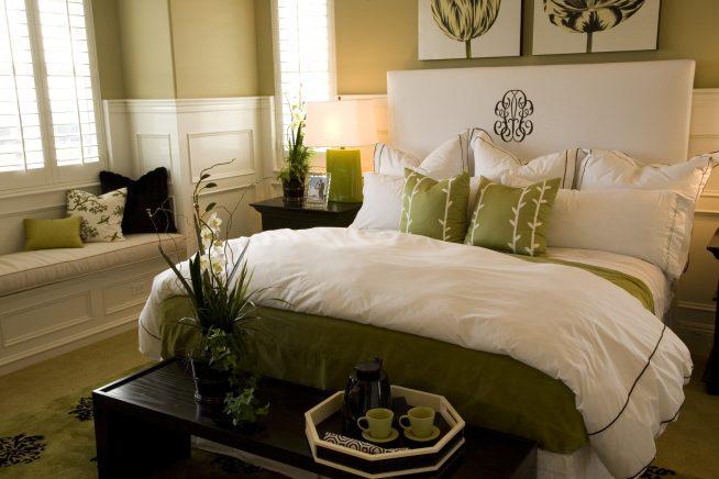 Кровать в спальне с одеялом и подушками белого и зеленого цветов