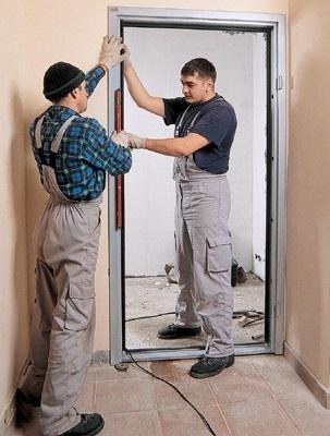 Рабочие устанавливают дверную коробку