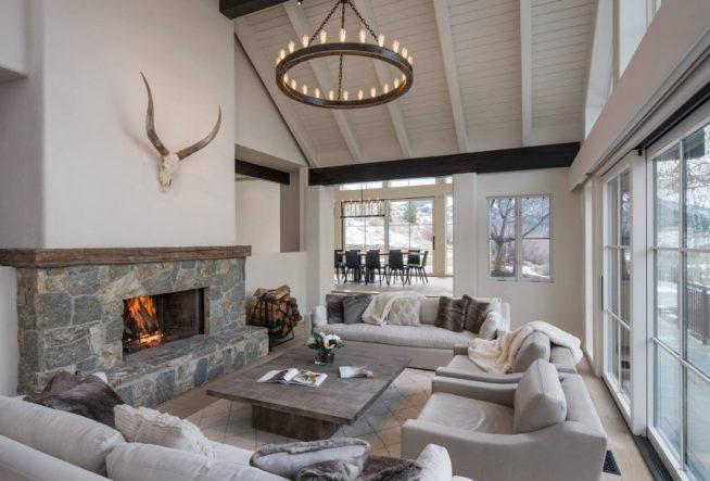 Дизайн просторной гостиной в светлых тонах с камином