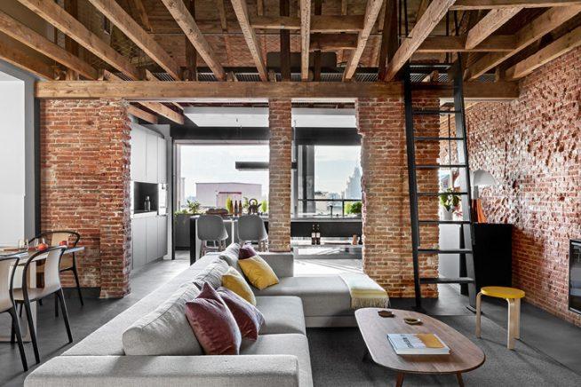 Дизайн просторной кухни-гостиной в стиле лофт с кирпичными стенами