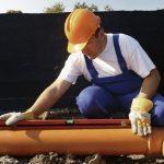 Рабочий делает систему канализации