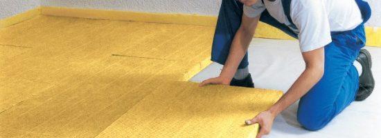 Рабочий укладывает теплоизоляционный материал на бетонный пол
