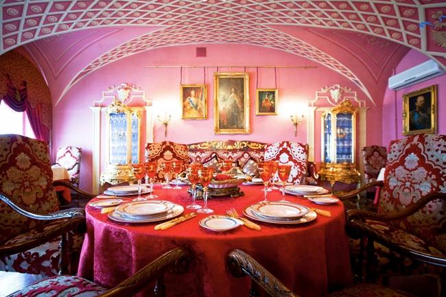 яркая столовая комната в розовых тонах, с большим количеством золотых рам для картин, интересным оформлением потолка, мягкими красными креслами с красивым узором