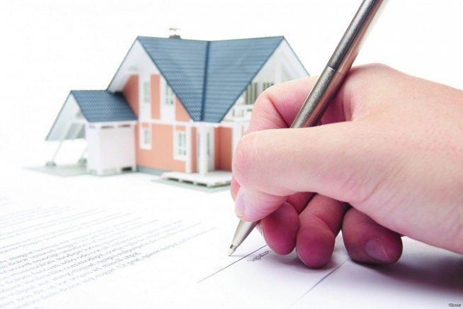 рука делает запись на листе бумаги, на втором плане изображен макет дома