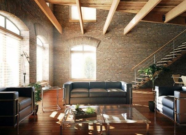 помещение в стиле лофт с лестницей, кожаными диванами, стекляным журнальным столиком