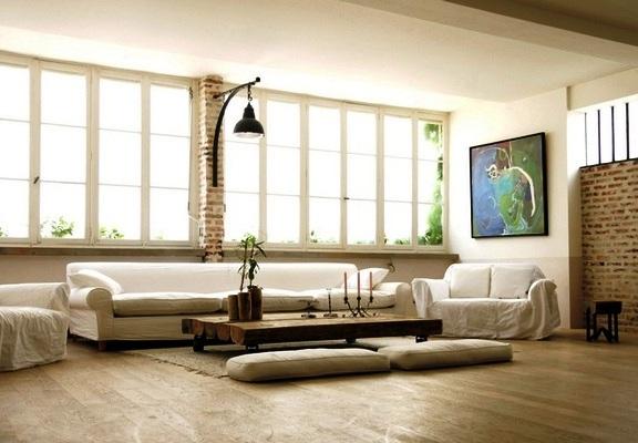 светлое помещение в стиле лофт, с крупными окнами, светлой мебелью, интересным светильником, картиной