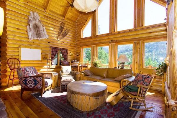 интерьер бревенчатого дома с большими окнами в бежево - желтых оттенках с деревянной и мягкой мебелью