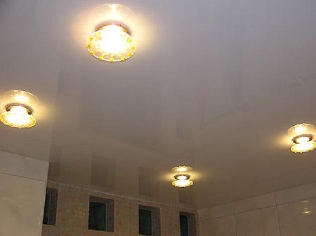 Симметричные светильники помогут скрыть повреждения натяжного потолка