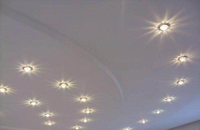 Точечные светильники, вмонтированные в натяжной потолок в несколько рядов
