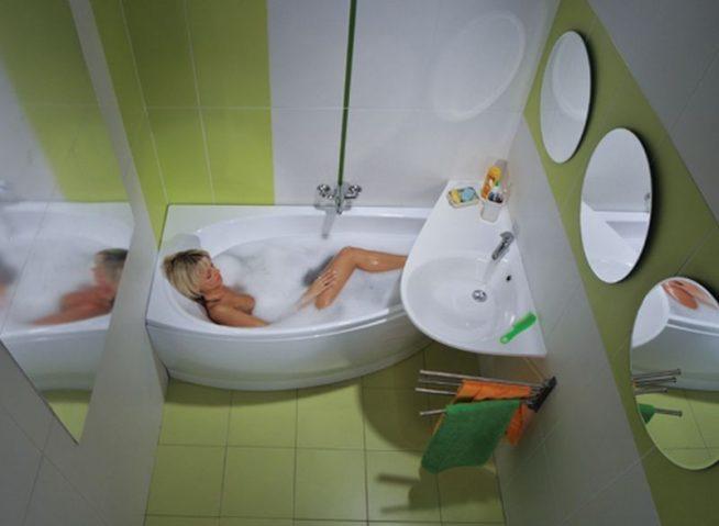 вид сверху на небольшую ванную комнату в зеленых тонах, где в ванной лежит девушка