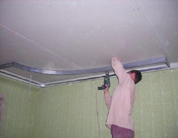 Мужчина крепит гипсокартон к потолку