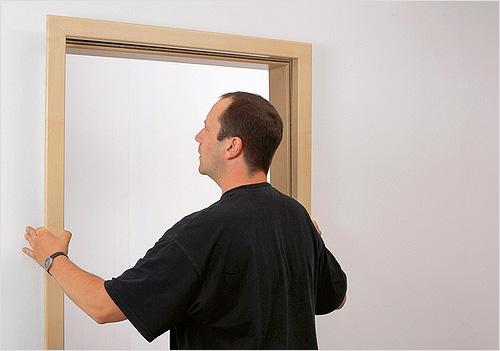 Мужчина проверяет правильность установки дверного короба