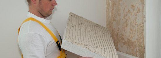 Рабочий крепит к стене звукоизоляционный материал