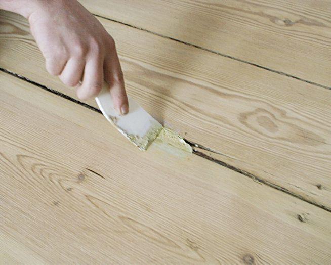 замазывание шпатлевкой щелей в деревянном полу