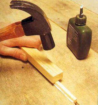 вбивание деревянных реек в щели деревянного пола