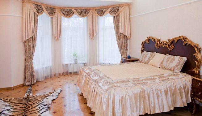 Просторная спальня с эркером и шторами из лёгкой ткани