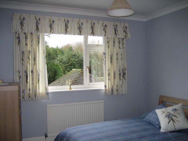 Узкий ламбрекен и корокие шторы в спальне с небольшим окном