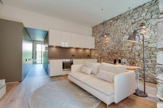 Интерьер кухни-гостиной с каменной стеной
