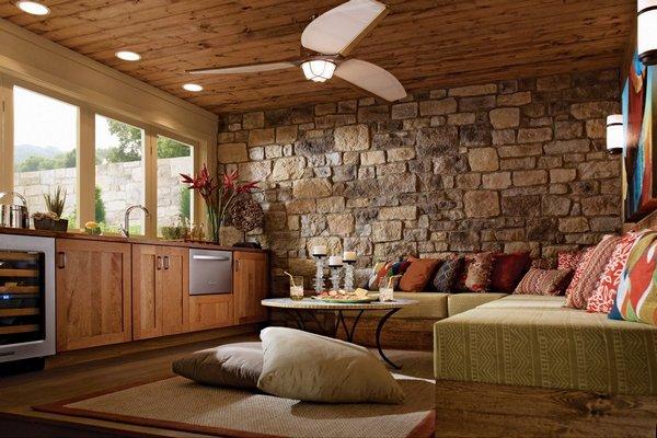Интерьер кухни-гостиной с массивной каменной стеной