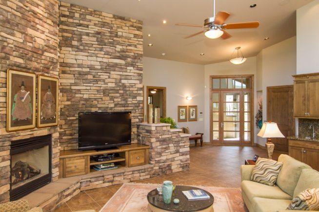 Интерьер гостиной с каменной стеной