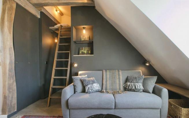 Спальня в мансардной квартире, оформленная в деревенском стиле