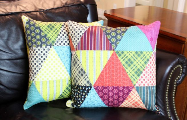 Диванные подушки, оформленные лоскутным шитьём, на кожаном диване