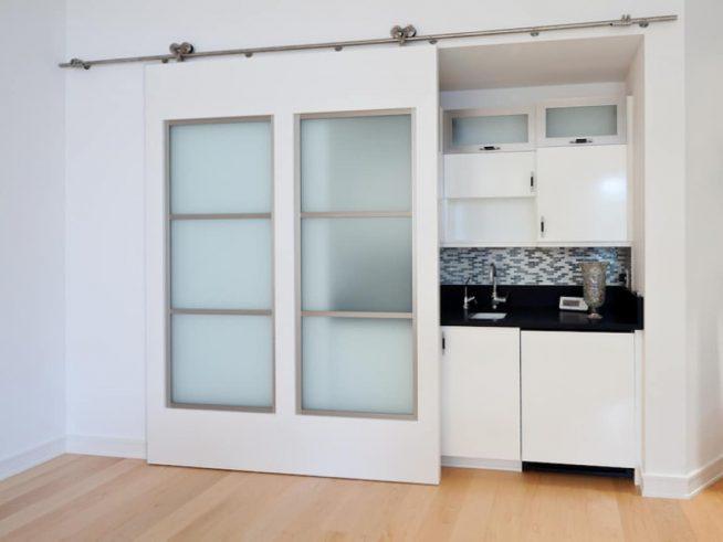 Раздвижная дверь, закрывающая кухню в маленькой студии
