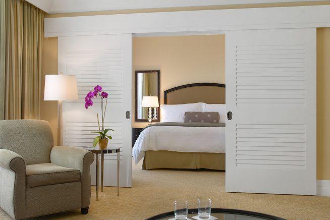 Белые глухие раздвижные двери между спальней и гостиной