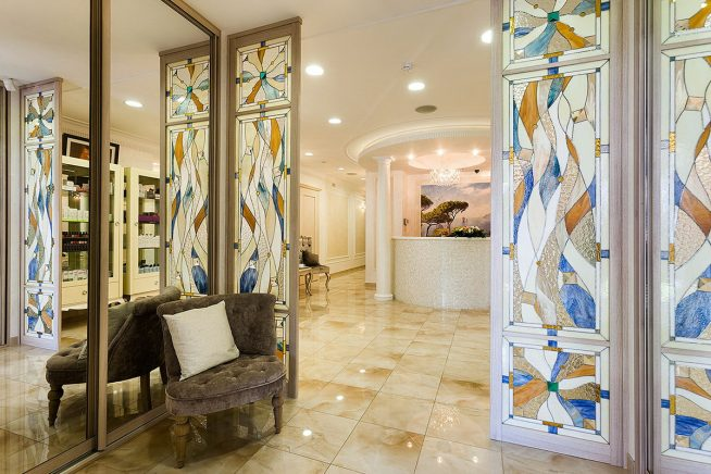 Складная дверь в гостиную, оформленная витражами