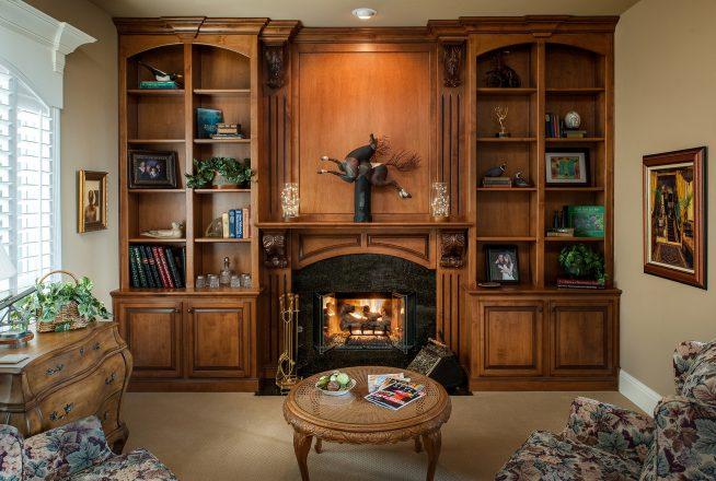 Деревянный книжный шкаф в интерьере гостиной