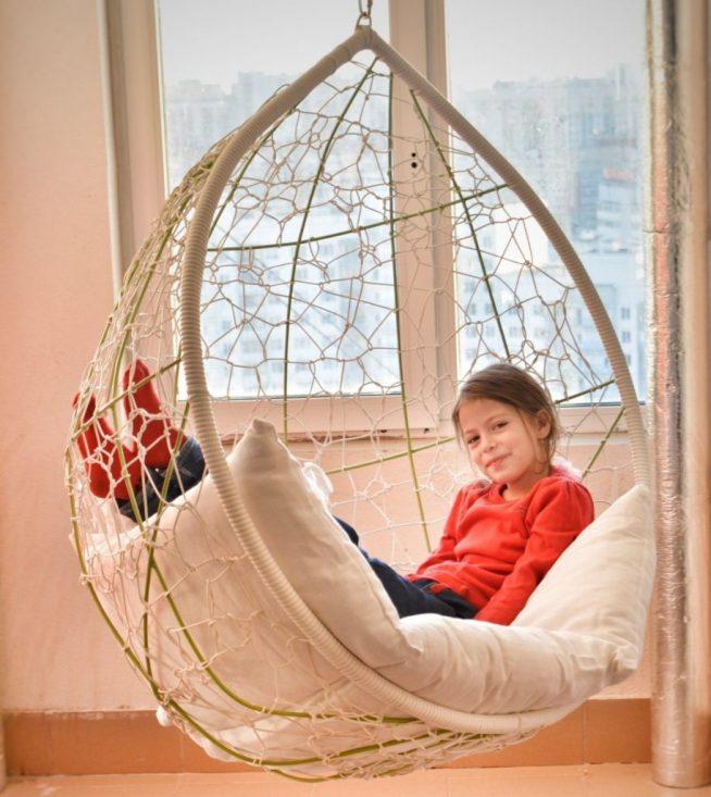 Девочка сидит в большом подвесном кресле в комнате