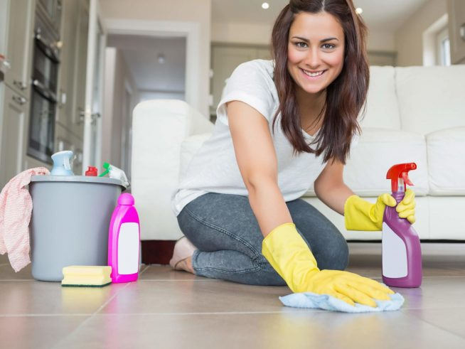 Девушка моет пол в резиновых перчатках