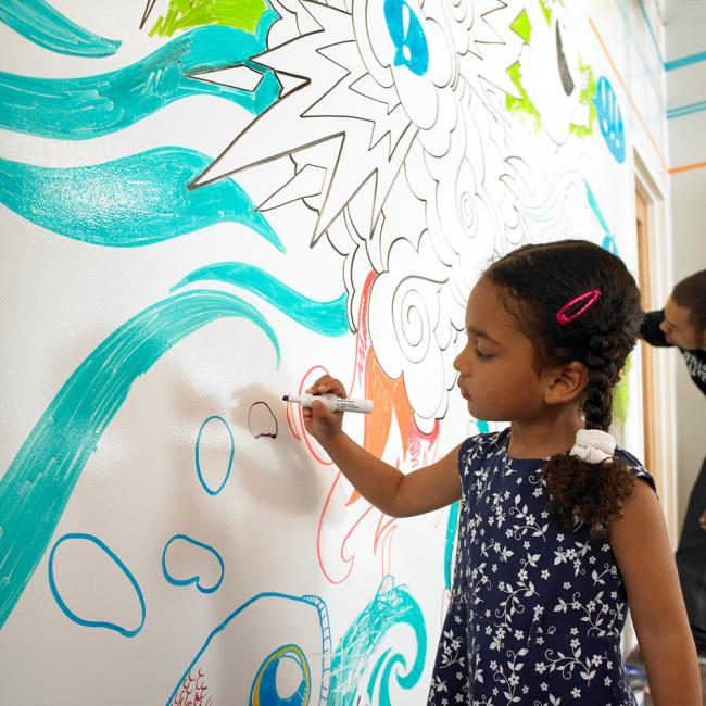 Девочка рисует на стене с маркерным покрытием