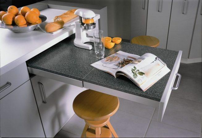 Выкатной обеденный столик и маленькие табуретки на кухне