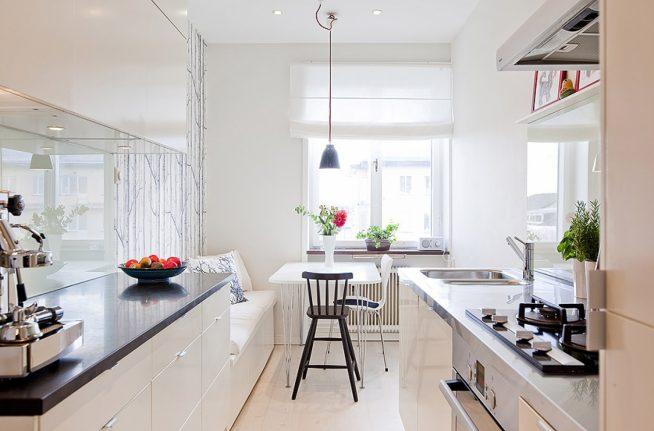 Интерьер узкой длинной кухни с окном в белых тонах